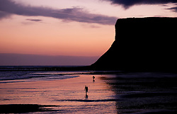 © Licensed to London News Pictures. 08/01/16<br /> Saltburn, UK. <br /> <br /> Surfers walk across the beach as day breaks over Saltburn beach.<br /> <br /> Photo credit : Ian Forsyth/LNP