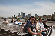 Tourists take a sightseeing tour cruise boat down the River Thames taking in some of the famous landmarks, skylines and iconic buildings in the capital, operated by City Cruises in London, England, United Kingdom.