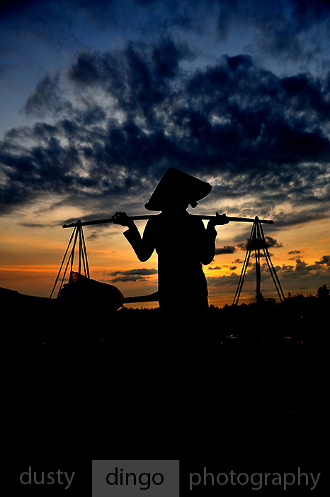 """Woman selling food from a """"don ganh"""" (two baskets slung from each end of a wooden or bamboo pole), silhouetted against pre-dawn sky. Red Sand Dunes, Mui Ne, Vietnam"""