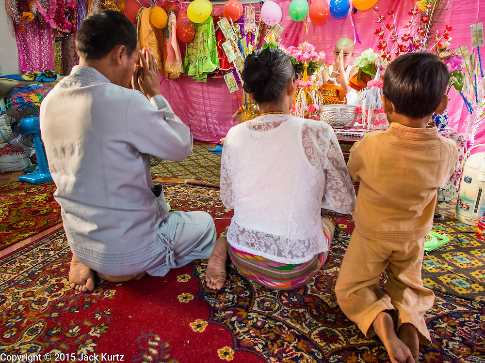 """04 APRIL 2015 - CHIANG MAI, CHIANG MAI, THAILAND: A family prays with a Tai boy in an alter in his family's living space at Wat Pa Pao during the Poi Sang Long Festival. The Poi Sang Long Festival (also called Poy Sang Long) is an ordination ceremony for Tai (also and commonly called Shan, though they prefer Tai) boys in the Shan State of Myanmar (Burma) and in Shan communities in western Thailand. Most Tai boys go into the monastery as novice monks at some point between the ages of seven and fourteen. This year seven boys were ordained at the Poi Sang Long ceremony at Wat Pa Pao in Chiang Mai. Poy Song Long is Tai (Shan) for """"Festival of the Jewel (or Crystal) Sons.      PHOTO BY JACK KURTZ"""