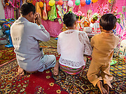 "04 APRIL 2015 - CHIANG MAI, CHIANG MAI, THAILAND: A family prays with a Tai boy in an alter in his family's living space at Wat Pa Pao during the Poi Sang Long Festival. The Poi Sang Long Festival (also called Poy Sang Long) is an ordination ceremony for Tai (also and commonly called Shan, though they prefer Tai) boys in the Shan State of Myanmar (Burma) and in Shan communities in western Thailand. Most Tai boys go into the monastery as novice monks at some point between the ages of seven and fourteen. This year seven boys were ordained at the Poi Sang Long ceremony at Wat Pa Pao in Chiang Mai. Poy Song Long is Tai (Shan) for ""Festival of the Jewel (or Crystal) Sons.      PHOTO BY JACK KURTZ"