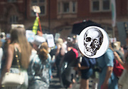 School Climate Strike, London, England, UK. An Extinction Rebellion sticker of a skull on a window with a reflection of the crowd.