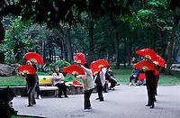 Women practice fan dancing in the park around in the early morning around Hoan Kiem Lake, Hanoi.