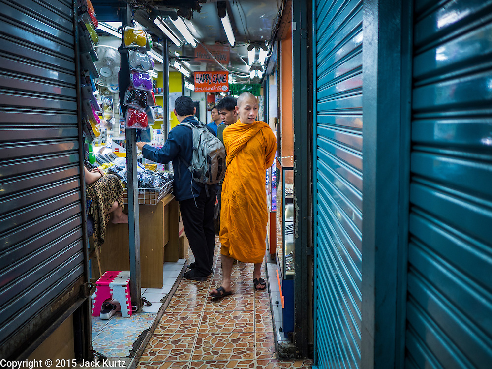 29 SEPTEMBER 2015 - BANGKOK, THAILAND:  A Buddhist monk walks through Saphan Lek market. Some of the shops in the market are already closed. Street vendors and illegal market vendors in the Saphan Lek area will be removed in the next two weeks as a part of an urban renewal project coordinated by the Bangkok Metropolitan Administration. About 500 vendors along Damrongsathit Bridge, popularly known as Saphan Lek, have 15 days to relocate. Vendors who don't move will be evicted. Saphan Lek is just one of several markets and street vending areas being closed in Bangkok this year. The market is known for toy and replica guns, bootleg and pirated DVDs and CDs and electronic toys.   PHOTO BY JACK KURTZ
