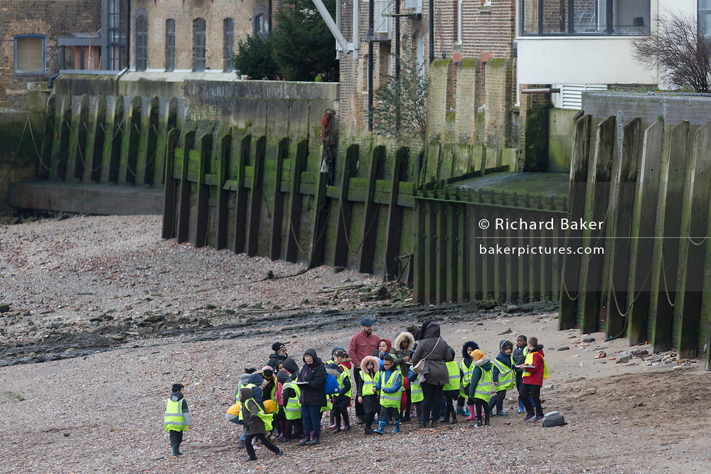 A party of schoolchildren make their way along the foreshore on the southern bank of the Thames at Rotherhithe, on 17th January 2020, in London, England.