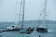 Newport, RI - Super yachts at the Newport Shipyard heal with the gusts against bare poles.  The evening high tide and the surge with it has floated them near the tops of the pilings during Hurricane Sandy in Newport, Rhode Island