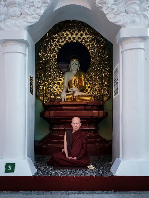 YANGON, MYANMAR - CIRCA DECEMBER 2017: Monk meditating at the Shwedagon Pagoda in Yangon