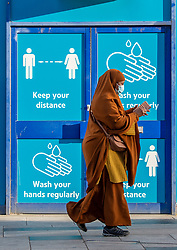 © Licensed to London News Pictures. 23/10/2020. Slough, UK. A woman holding a mobile phone walks past an empty shop entrance with coronavirus safety advice covering the windows. Slough will move to Local COVID Alert Level: High (Tier 2) at 00:01 BST on Saturday 24th October 2020 after an increase in people infected with the COVID-19 coronavirus. Photo credit: Peter Manning/LNP