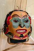 """This modern Tlingit """"War Helmet"""", made in 2010 by master carver Wayne Price, has human hair covering the back, with sea lion whisters at top. Sheldon Museum and Cultural Center, Haines, Alaska, USA. This interesting museum showcases the art and culture of Haines, with over 4000 artifacts including Chilkat Blankets, Eldred Rock lighthouse lens, 12,000 cataloged photographs from the 1800s until today; books and countless documents. <br /> https://www.sheldonmuseum.org/"""