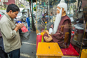 22 JANUARY 2013 - BANGKOK, THAILAND:  A man prays at the shrine of a revered Chinese monk on Yaowarat Road in Bangkok's Chinatown.      PHOTO BY JACK KURTZ