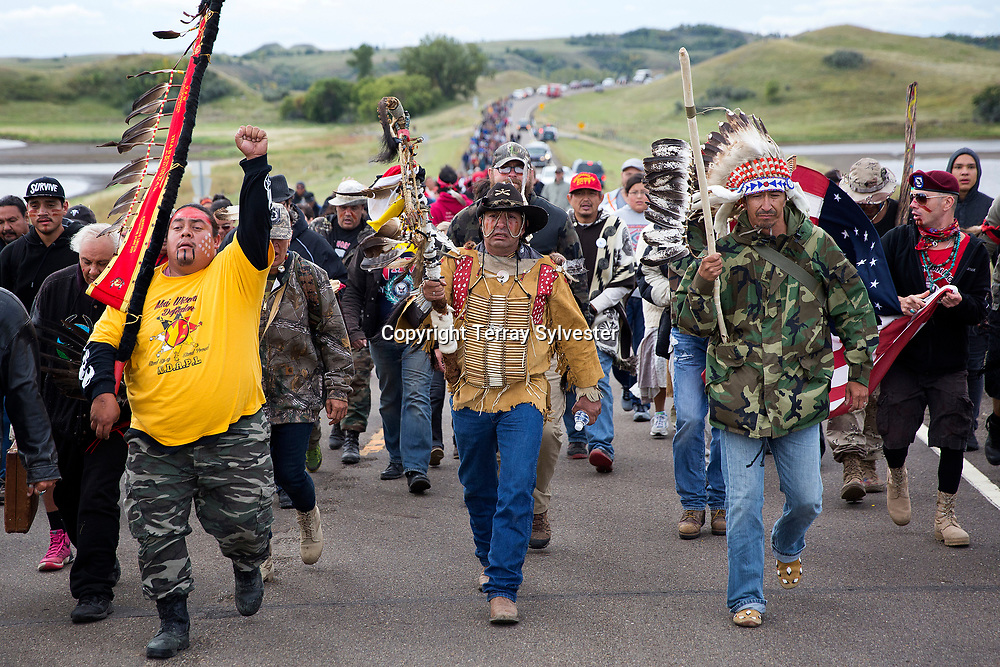 Greg Cournoyer of the Yankton Sioux Tribe, Steven Gray of the Cheyenne River Sioux Tribe, and Catcher Cuts the Rope from the Fort Belknap Reservation in Montana (from left) lead a march to the Dakota Access oil pipeline route on September 9, 2016. Cannon Ball, North Dakota, United States.