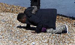 © Licensed to London News Pictures. 22/09/2021. Dungeness, UK. A migrant kisses the beach at Dungeness in Kent after being rescued by the RNLI as he crossed the English Channel. Hundreds of migrants have made the crossing in the calm weather this week. Photo credit: Sean Aidan/LNP