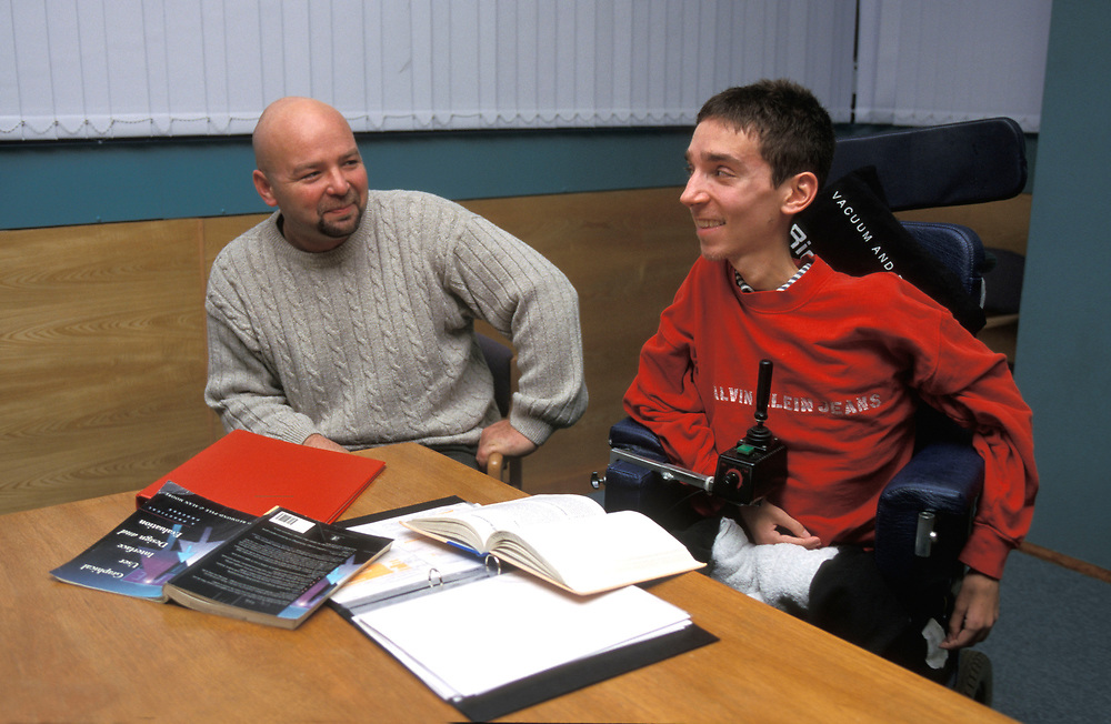 Disabled University student with carer studying,