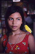 CHILDREN PETS. Rocinha Favela, Rio de Janeiro, Brazil, South America. Young teenage girl with budgerigar, common pet parakeet, known as budgie. Although Rocinha is technically classified as a neighborhood, many still refer to it as a favela. It developed from a shanty town into an urbanized slum. Today, almost all the houses in Rocinha are made from concrete and brick. Some buildings are three and four stories tall and almost all houses have basic sanitation, plumbing, and electricity. Compared to simple shanty towns or slums, Rocinha has a better developed infrastructure and hundreds of businesses. There is also lots of deliquency, crime and drugs in the favelas.