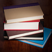Five hardcover books stacked on a wooden table.