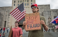 """'Stop the Steal' rally in Baton Rouge, LA on Nov. 7 a couple hours after Biden was declared the winner in the 2020 election against Trump.  Trump supporters believe that the election was stolen and that Trump won.  """"Stop the Steal' rally's were held at State capitols acorss the country. Lenny & Marlene Stelly holding the flag they flew throughout the Trump years at a 'Stop the Steal' rally in Baton Rouge, LA.  The 'Stop the Steal' rally in Baton Rouge, LA on Nov. 7 held  a couple hours after Biden was declared the winner in the 2020 election against Trump.  Trump supporters believe that the election was stolen and that Trump won.  """"Stop the Steal' rallies were held at State capitols acorss the country."""