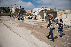 2 March 2020, Hebron: Daniel from Switzerland and Nora from Finland, both participants in the Ecumenical Accompaniment Programme in Palestine and Israel walk down Al-Shuhada Street in the H2 area of Hebron. The area is under Israeli military control, and following the 1994 massacre at the Tomb of the Patriarchs (known to the Muslims as Al-Ibrahimi Mosque and to the Jews as Cave of Machpelah) all the Palestinian shops on Shuhada street have been closed, turning the street into a virtual ghost town.