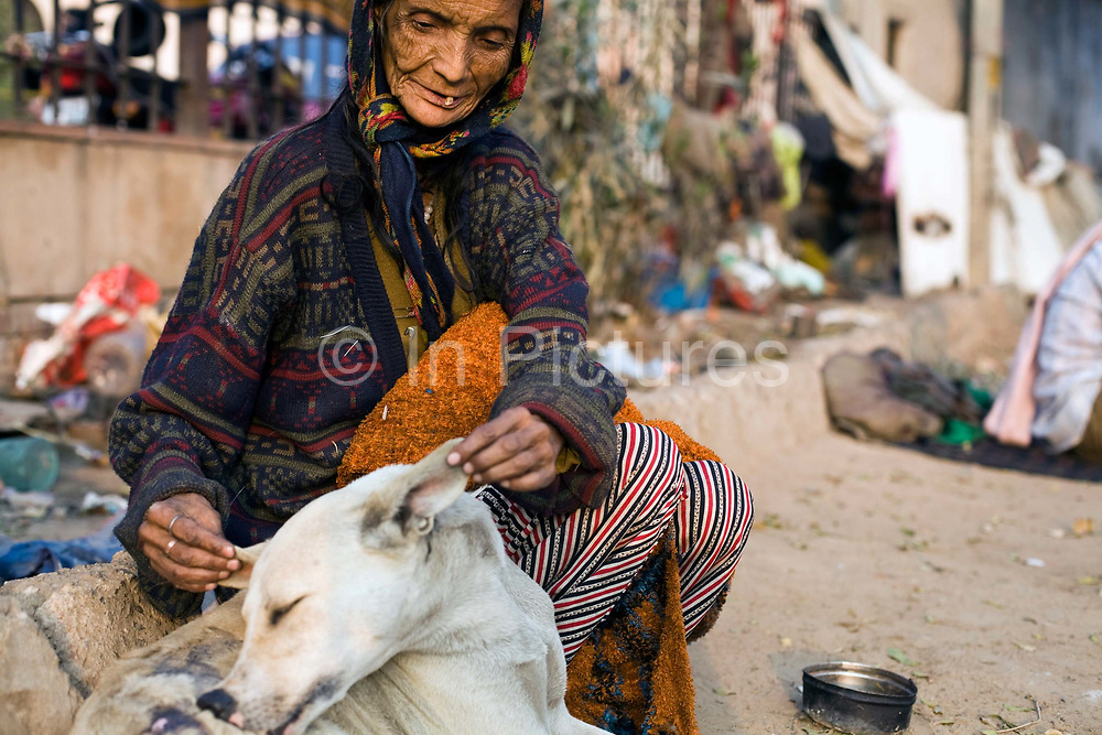 """Kathleen Lama, 70, a homeless woman, fusses over a stray dog. Originally from Darjeeling she has now made her home on a patch of land in Nizamuddin, Delhi, India.""""I came to Delhi with my husband in 1965. We lived for some time in Old Delhi and then we had bad luck and became homeless. I don't want to leave here because my husband died in this place and anyway, I serve all the animals here now."""""""