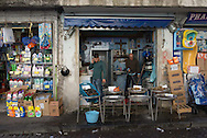 A man talks on a phone while another washes the ground outside the store at a roadside shop in Naples, Italy