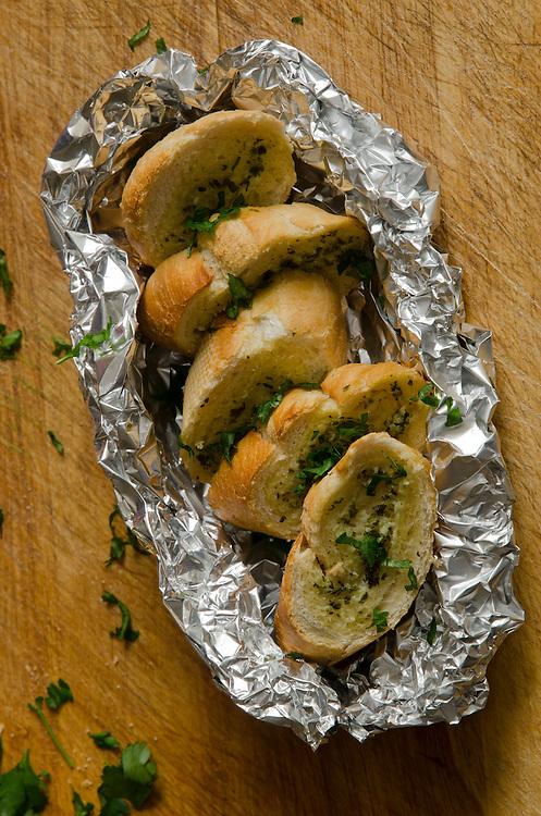 Hot cheesy herby garlic bread on a wooden board