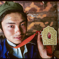CHINA, TIBET. Young Tibetan Buddhist man (a Menba) in remote village near Tsangpo River Gorge displays charm box with forbidden photo of Dalai Lama.