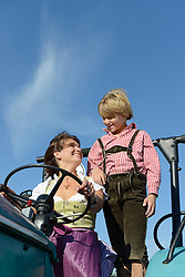 Mother and son driving tractor, Bavaria, Germany