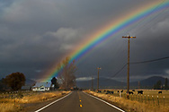 Rainbow over rural country road and farm house in the Hat Creek Valley, Shasta County, California