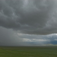 MONGOLIA. Gathering storm clouds and rain squall cross a remote valley east of Muren.