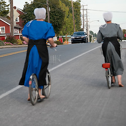 Bird-in-Hand, PA - September 28, 2014: Two barefoot Amish women riding bicycles on the main road in the Lancaster County village.