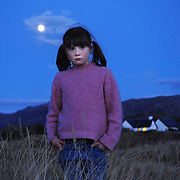 A young girl looks out over Loch Morar at twilight, as the moon rises. .       Robert Perry Scotland on Sunday 11th April 2008