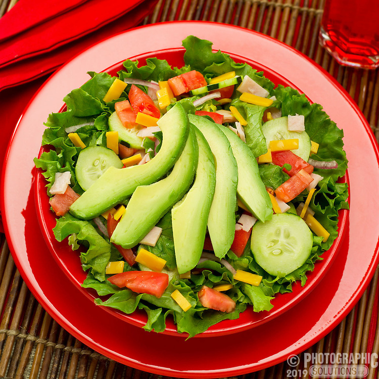 An avocado salad with lettuce, tomato and cheese
