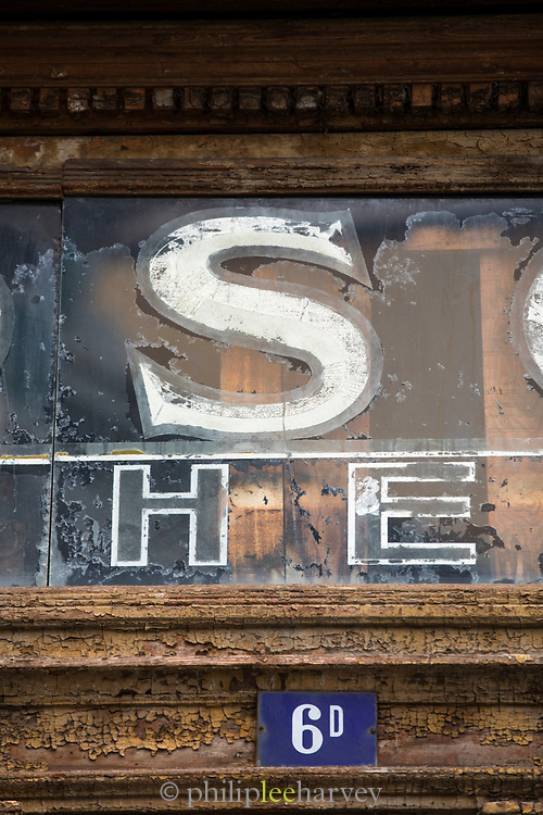 Close-up of weathered shop front sign detail on wall, Trieste, Italy