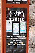 Self service buying of wine and fruit juice at a winery and farm. A display with wine bottles and olive oil. Potmje village, Dingac wine region, Peljesac peninsula. Dingac village and region. Peljesac peninsula. Dalmatian Coast, Croatia, Europe.