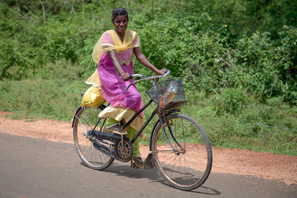 A woman rides her bike in Akkarayankulam, Kilinochchi, Sri Lanka.
