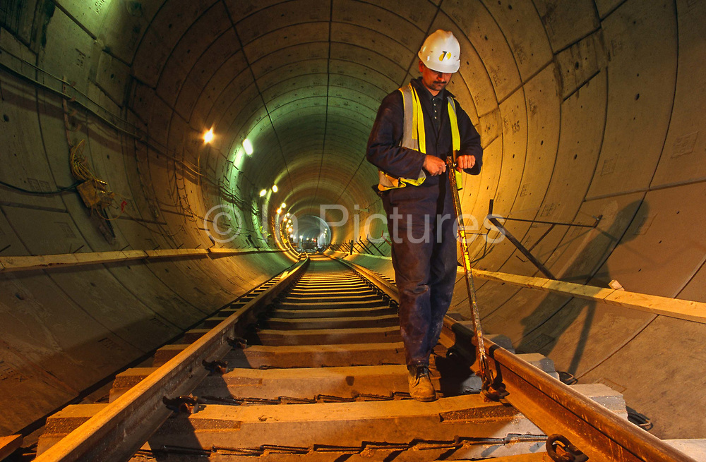 An engineer working underground during construction of the Heathrow Express train project on behalf of Heathrow airport operator BAA (British Airport Authority), London England. While standing erect, he twists a high-tension tool that secures the concrete sleepers to the steel rails using a Pandrol Clip. The tunnel snakes its way into the distance behind him, lit by temporary lighting on the 5-mile tunnel wall. Its sections are reinforced concrete, shaped for the Heathrow Express electric Siemens-built trains that provide a direct link between Heathrow's terminals and Paddington station in central London. This is now the most expensive rail-mile fare in the UK at £15.50 for a 15-minute journey. In 1994 one tunnel collapsed without warning in one of the most catastrophic civil engineering disasters in British history.