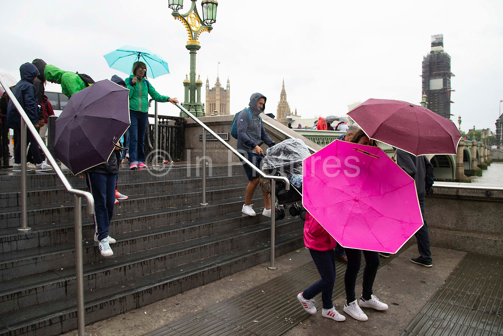 A childs pink umbrella turns inside out  during heavy rain fall and windy weather on Westminster Bridge in London, United Kingdom on 16th August 2019.