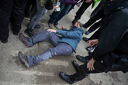 © Licensed to London News Pictures. 11/10/2017. Lancashire, UK.  A protester is pushed to the ground as police kettle protesters at the Anti-Fracking Demonstration in Kirby Misperton, Yorkshire. The protest blocked the entrance to Third Energy's Hydraulic fracking site after they were granted permission to set up their drilling rig at the site.  Photo credit: Steven Speed/LNP