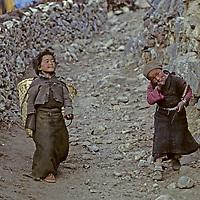 HIMALAYA, NEPAL. Sherpa girls head out to gather firewood in Dramo village, Khumbu region. Note khukri knife & tumpline basket.