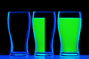 Three glasses, one empty, another half full and one full of glowing green fluid.Black light