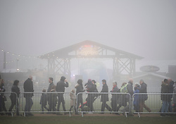 © Licensed to London News Pictures. 17/12/2016. London, UK. Visitors to Hyde Park pass the entrance to Winter Wonderland - almost hidden in the fog.  Parts of the UK are swathed in thick fog this morning. Photo credit: Ben Cawthra/LNP
