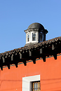A cupola above a tyiles toof and a red plastered wall, Antigua Guatemala, Republic of Guatemala.