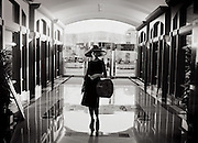 A woman is dressed up and ready to go shopping, standing in the lobby of her hotel
