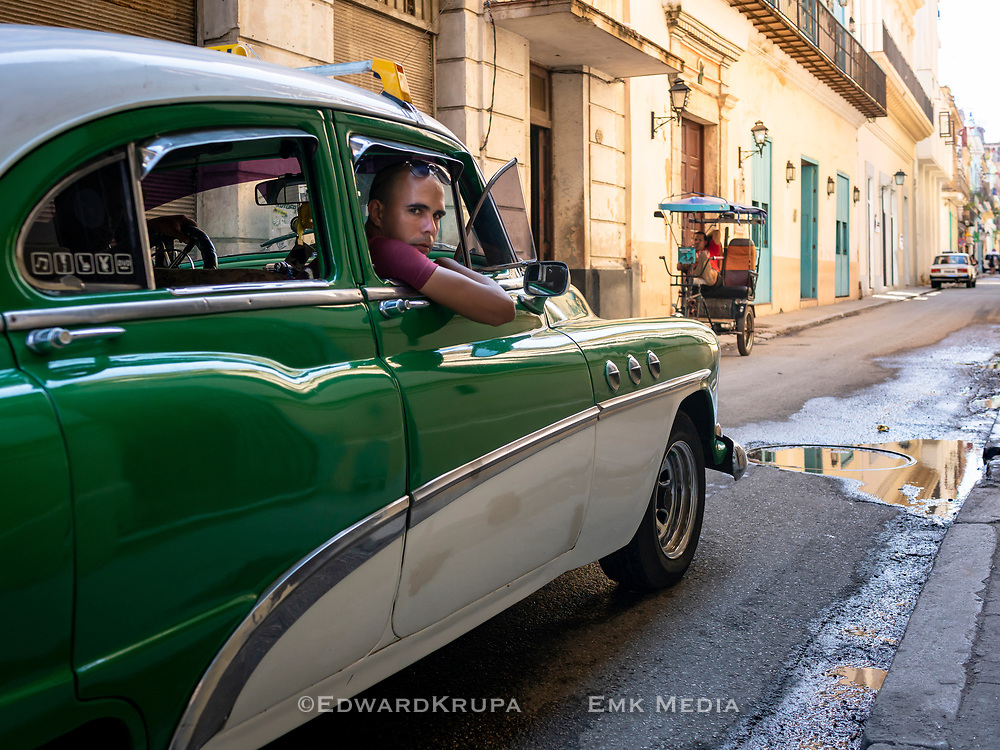 Cruising for a fare in an classic car taxi in Havana, Cuba.