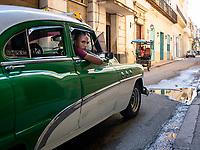 Cruising for a fare in an classic car taxi in Havana, Cuba.