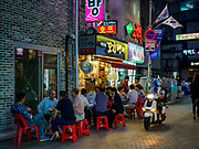 SEOUL, SOUTH KOREA: Men sit outside and eat at a Korean barbecue shop in Seoul.       PHOTO BY JACK KURTZ