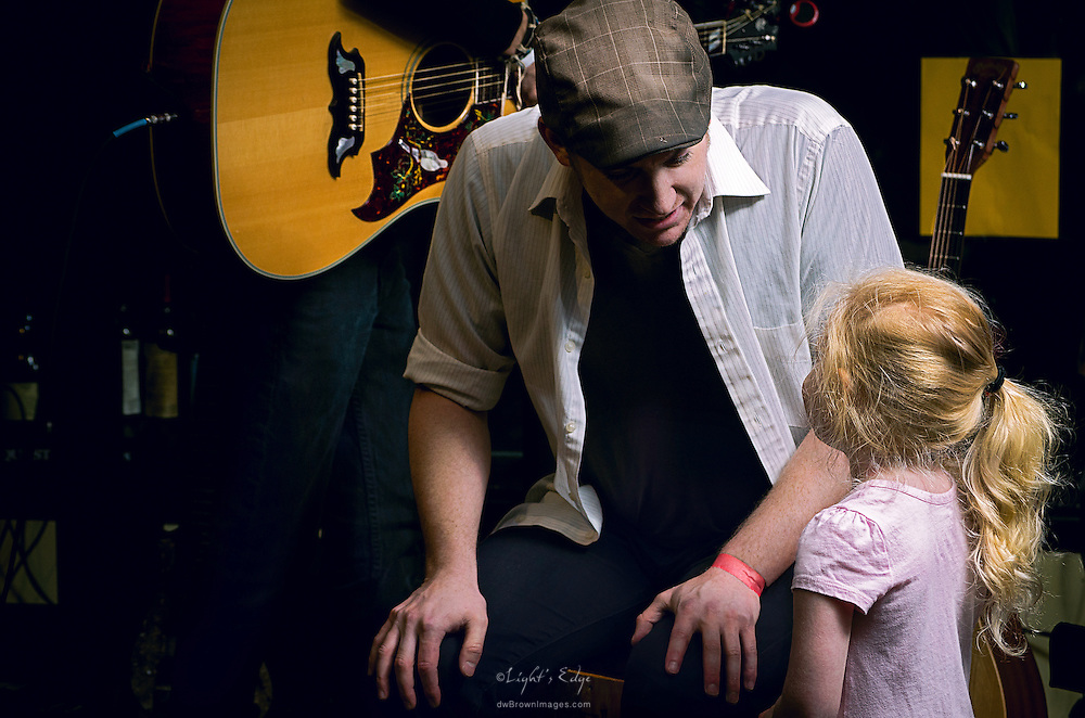 Josh Mayer listening to his neice at the beginning of a benefit performance for the creation of a music school in Guatemala. The benefit was held at The Bus Stop Music Cafe in Pitman, NJ.