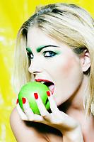 beautiful caucasian woman portrait eating an apple studio on yellow background