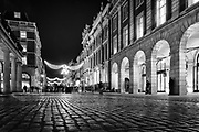 Christmas lights reflect in the cobblestones at Covent Garden. An nighttime urban scene captured in London, England's capital city.