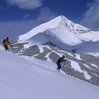 SKIING, Big Sky, Montana. Patrick Shanahan & Maclaren Johnson ski off Andesite Mountain with Lone Mountain in background.