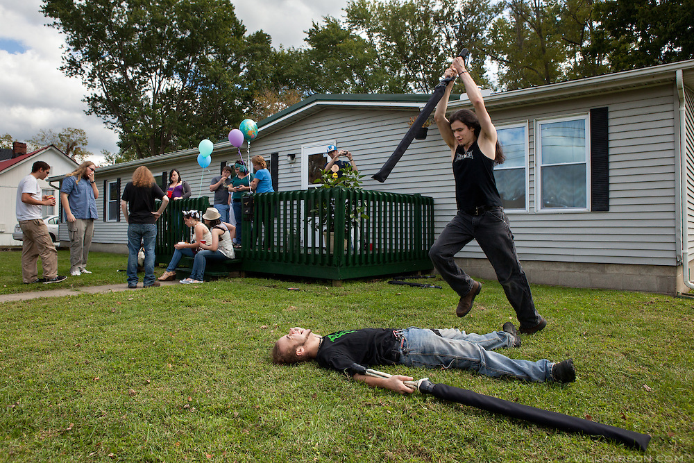 """Anthony Rohn of Athens, Ohio, gleefully awaits a death blow dealt by Cory Medina, of Richmond, Va., during a fake sword fight at the 22nd birthday party of Ravan Garland, also of Athens, shown wearing a tiara on her front step in Athens on Sept. 17, 2011. Friends from four states converged in Athens for the celebration. Garland says, """"We're all crazy. There's more crazy when everyone gets together."""""""